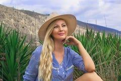 Mulher loura bonita em um chapéu Senta-se fora na pradaria Misteriosamente sorrindo foto de stock royalty free