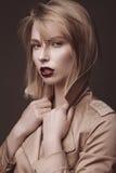 Mulher loura bonita em um revestimento brilhante e em uns bordos escuros, mostrando poses diferentes Face da beleza Fotos de Stock