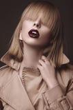 Mulher loura bonita em um revestimento brilhante e em uns bordos escuros, mostrando poses diferentes Face da beleza Fotografia de Stock Royalty Free