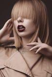 Mulher loura bonita em um revestimento brilhante e em uns bordos escuros, mostrando poses diferentes Face da beleza Foto de Stock