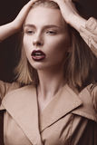 Mulher loura bonita em um revestimento brilhante e em uns bordos escuros, mostrando poses diferentes Face da beleza Imagem de Stock
