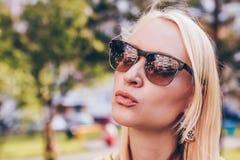A mulher loura bonita em vidros de sol d?-lhe um beijo Conceito lifestile engra?ado fotografia de stock royalty free