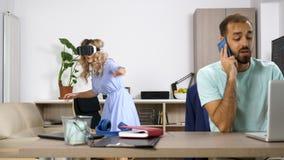 A mulher loura bonita explora a realidade virtual quando seu sócio falar no telefone celular video estoque