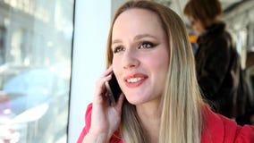 Mulher loura bonita feliz que senta-se no bonde, telefone de resposta video estoque