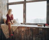 A mulher loura bonita guarda uma caixa de presente em seus olhares da mão fora da janela foto de stock royalty free