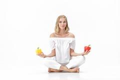 A mulher loura bonita na blusa branca escolhe a pimenta de sino amarela ou vermelha Saúde e dieta Fotografia de Stock