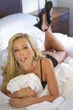 Mulher loura bonita na cama na roupa interior preta Fotos de Stock Royalty Free