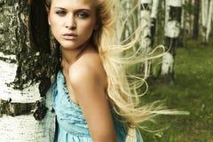 Mulher loura bonita na floresta. cabelo do voo Imagem de Stock