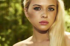 Mulher loura bonita na floresta. luz solar do verão Fotografia de Stock