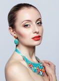 Mulher loura bonita no bijouterie no fundo cinzento Fotos de Stock Royalty Free