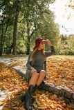 Mulher loura bonita no vestido cinzento da malha e no chapéu vermelho que sentam-se no th Imagem de Stock Royalty Free
