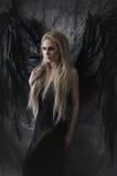 Mulher loura bonita no vestido preto com asas pretas imagens de stock
