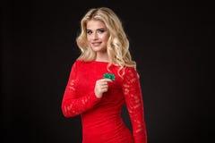 Mulher loura bonita nova com as microplaquetas de pôquer sobre o preto poker Fotos de Stock