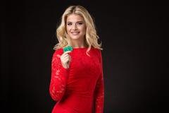 Mulher loura bonita nova com as microplaquetas de pôquer sobre o preto poker Imagens de Stock