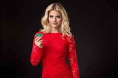 Mulher loura bonita nova com as microplaquetas de pôquer sobre o preto poker Imagens de Stock Royalty Free
