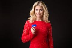 Mulher loura bonita nova com as microplaquetas de pôquer sobre o preto poker Fotografia de Stock Royalty Free