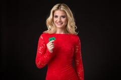 Mulher loura bonita nova com as microplaquetas de pôquer sobre o preto poker Foto de Stock Royalty Free