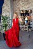 Mulher loura bonita nova do retrato no vestido de noite vermelho na mulher interior da sessão fotográfica do sótão no vestido de  Foto de Stock