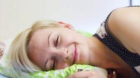 Mulher loura bonita nova que dorme em sua cama na manhã video estoque