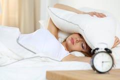 Mulher loura bonita nova que encontra-se na cama que sofre do alarme c Fotos de Stock Royalty Free