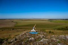 A mulher loura bonita nova que faz a ioga exercita em uma rocha Imagens de Stock Royalty Free