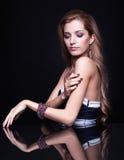 Mulher loura bonita nova que senta-se na tabela do espelho em vagabundos pretos Imagem de Stock Royalty Free