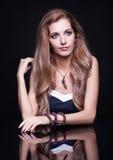 Mulher loura bonita nova que senta-se na tabela do espelho em vagabundos pretos Imagem de Stock