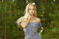 Mulher loura bonita que anda na floresta. verão Fotografia de Stock