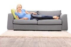 Mulher loura bonita que encontra-se em um sofá cinzento moderno Foto de Stock