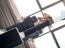 Mulher loura bonita que escuta a música ao descansar no sofá fotografia de stock royalty free