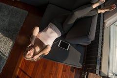 Mulher loura bonita que escuta a música ao descansar no sofá fotos de stock royalty free