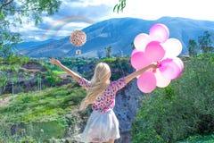 Mulher loura bonita que está e que olha uma paisagem bonita e montanhas com um arco-íris imagem de stock