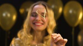 Mulher loura bonita que guarda a luz de bengal coração-dada forma no partido, celebração vídeos de arquivo
