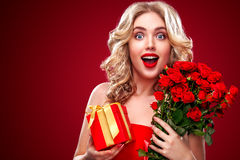Mulher loura bonita que guarda o ramalhete de rosas vermelhas e de presente Valentim de Saint e dia internacional do ` s das mulh fotografia de stock