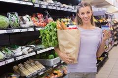 Mulher loura bonita que guarda o saco e o cartão de crédito Foto de Stock