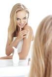Mulher loura bonita que olha em um espelho ao espalhar o corpo fotos de stock royalty free