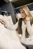 Mulher loura bonita que olha o preço do vestido de casamento no boutique nupcial Fotos de Stock Royalty Free