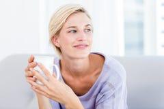 Mulher loura bonita que relaxa no sofá e que guarda uma caneca Fotografia de Stock Royalty Free