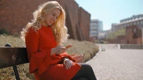 Mulher loura bonita que senta-se em um banco e que usa seu telefone esperto móvel App filme