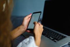 Mulher loura bonita que telefona com seu smartphone que encontra-se em sua cama ao lado de seu caderno Menina que encontra-se na  fotografia de stock