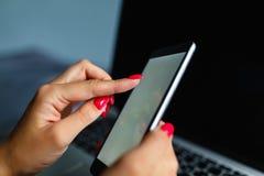 Mulher loura bonita que telefona com seu smartphone que encontra-se em sua cama ao lado de seu caderno Telefone celular com a tel imagens de stock
