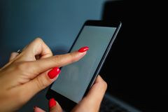Mulher loura bonita que telefona com seu smartphone que encontra-se em sua cama ao lado de seu caderno Telefone celular com a tel foto de stock