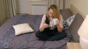 Mulher loura bonita que veste o terno formal que senta-se na cama, smartphone do uso e bebendo o café vídeos de arquivo