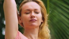 A mulher loura bonita toca em seu cabelo na natureza Vista traseira Conceito do tratamento do cabelo vídeos de arquivo