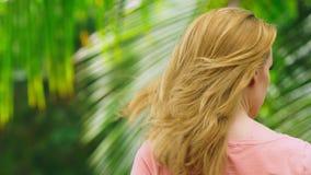 A mulher loura bonita toca em seu cabelo na natureza Vista traseira Conceito do tratamento do cabelo filme