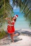 A mulher loura bonito no vestido, em óculos de sol e no chapéu vermelhos de Santa está na palmeira na praia tropical exótica Conc Fotos de Stock