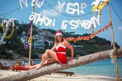Mulher loura bonito no vestido, em óculos de sol vermelhos e no chapéu de Santa que senta-se na palmeira na praia tropical exótic Imagem de Stock Royalty Free