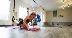 Mulher loura carismática que praticam os exercícios aeróbios que esticam o corpo e pés usando um elástico em um moderno equipado video estoque