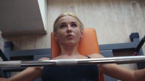Mulher loura caucasiano no treinamento preto do sutiã do esporte com a barra no banco no gym com janelas panorâmicos Concentrado  vídeos de arquivo