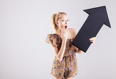 Mulher loura chocada com seta imagem de stock royalty free